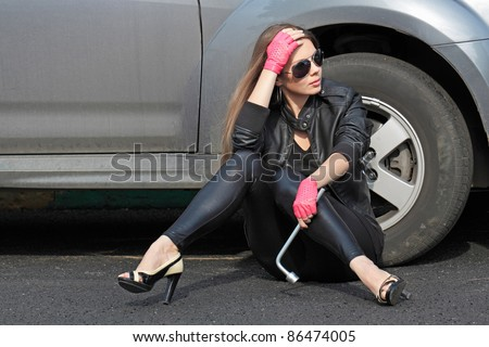The girl with a wrench sitting on the pavement near the malfunctioning of the car