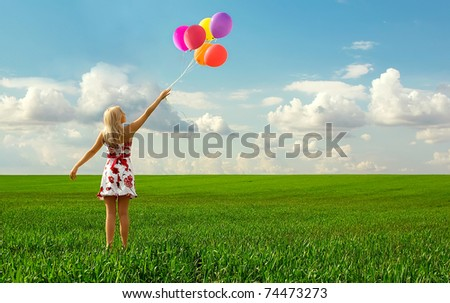 The girl with balloons plays in a field - stock photo