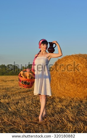 The girl with bread, a long loaf and milk on a mow - stock photo