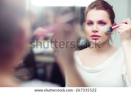 The girl with bright pink a make-up applies blush near a mirror. She touches with a brush a cheek. Studio portrait. - stock photo
