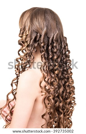 The girl with brown long curly hair isolated on white background.