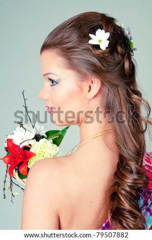 The girl with flowers in a bright dress on a gray background - stock photo