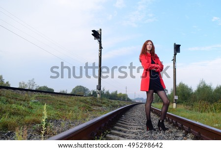 the girl with long hair standing on the railroad in the red coat nature