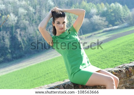 the girl with the green dress sitting on a wall of the castle while collecting her hair - stock photo