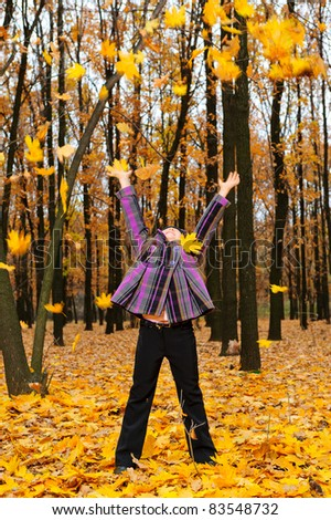 The girl with the lifted hands autumn forest. Falling yellow leaf - stock photo