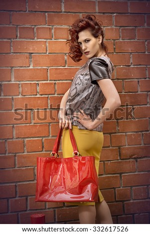 The girl with the red bag by the brick wall