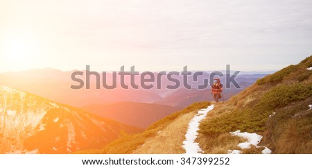 The girl with the rucksack moves along a mountain trail.