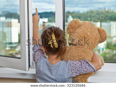 The girl with the toy stands at an open window - stock photo