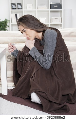 The girl wrapped in a blanket sitting on the floor in the living room holding a thermometer in hand