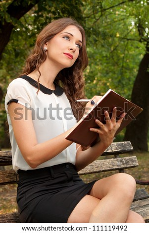 The girl writes her diary in the park - stock photo