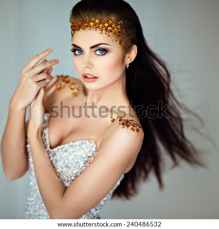 The glamorous portrait of a beautiful girl brunette with sequins on the face, close up - stock photo