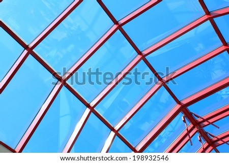 The glass roof structure, blue sky - stock photo