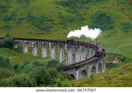 the Glenfinnan Viaduct in Scotland with the Jacobite steam train at summer time - stock photo