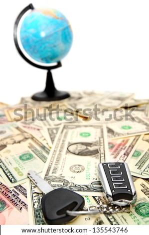 The globe and keys from the car on dollars. - stock photo