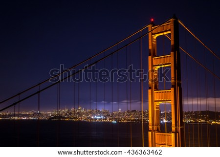 The glowing city of San Francisco through the Golden Gate Bridge tower at night - stock photo