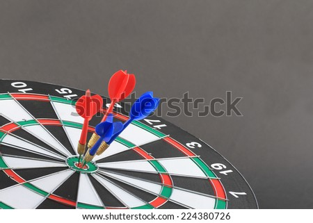 The goal of business is intended to accomplish as a team darts on dark gray background with arrows, middle target.  - stock photo