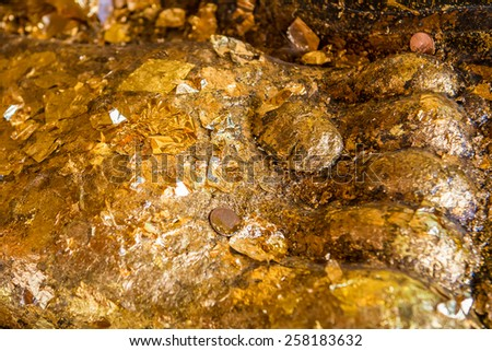 The gold leaf on Buddha statue in temple of Thailand. For the background and textures. - stock photo