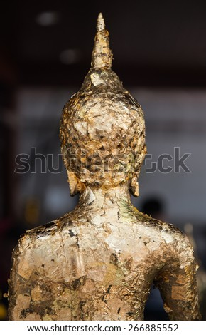 The gold leaf on the back of Buddha statue in temple of Thailand. - stock photo