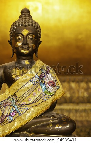 The golden black buddha statue in the setting posture. - stock photo
