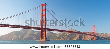 The Golden Gate Bridge in San Francisco during the sunset with beautiful azure ocean in background panorama - stock photo