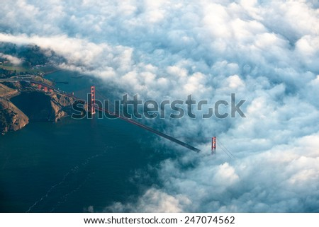 The Golden Gate Bridge rises through dramatic early morning fog seen from above - stock photo