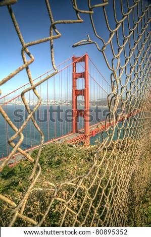 The Golden Gate Bridge through a chain link fence - stock photo