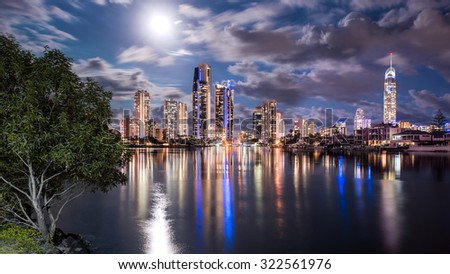 The Golden Gold Coast Skyline During A Full Moon Illuminating The Landscape With A Reflection In The Calm Water, Surfers Paradise, Queensland, Australia - stock photo