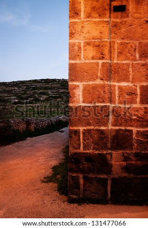 The golden light of a street lamp on a wall, dirt track leading up to the country side behind. - stock photo