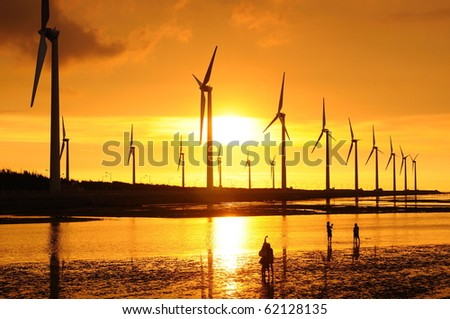 the golden sunset at the wind-power station - stock photo