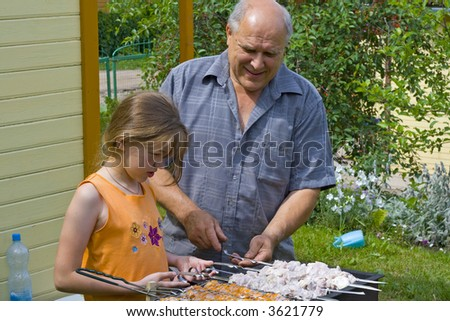 The grandfather learns the granddaughter to do a kebab