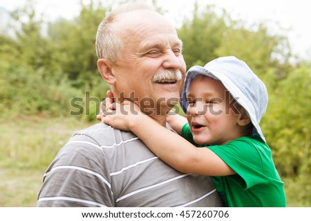 the grandfather plays with the grandson on shoulders in park