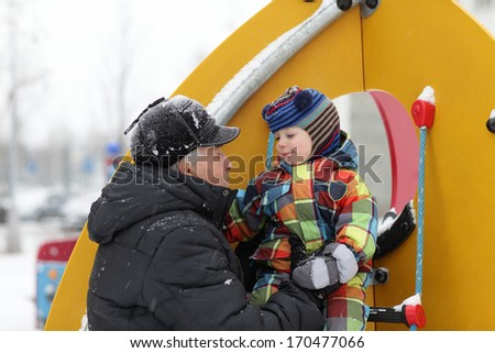 The grandfather with his grandson playing at winter playground - stock photo