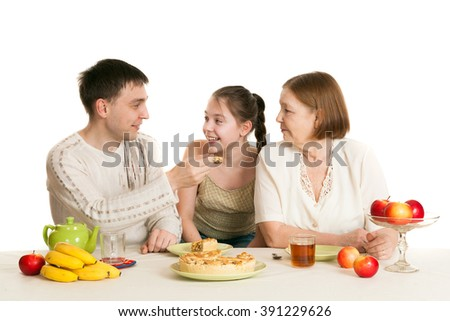 the grandmother and the granddaughter treat the father with pie and tea at a table