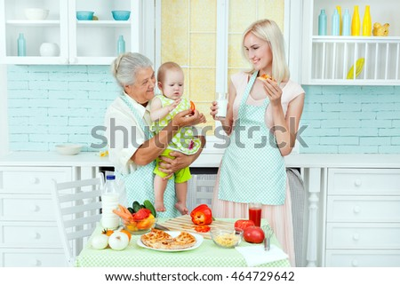 The grandmother holds the child on hands, mother stands nearby and eats.
