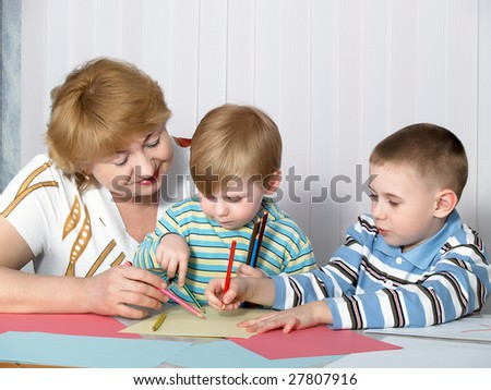 The grandmother is engaged in drawing with two grandsons