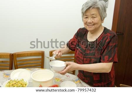 The grandmother is preparing dinner - stock photo