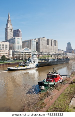 The 2012 Great Lakes shipping season gets underway as a tugboat and barge sail up the Cuyahoga River past the Tower City Complex in Cleveland, Ohio as a moored small tug awaits her next assignment - stock photo