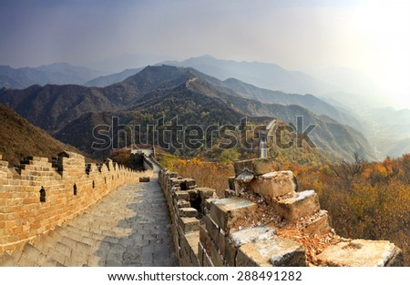 The Great Wall of China in Mutianyu mountains going high on hill tops in panoramic view from brick steps down to zigzag fortification - stock photo