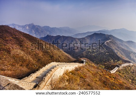The Great Wall of China near Mutianyu north from Beijing top of mountains brick wall zigzag doing down and away through yellow autumn forests - stock photo