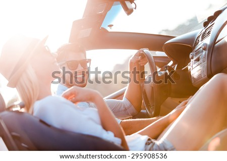 The greatest day for the road trip. Happy young couple smiling while sitting inside of their convertible - stock photo