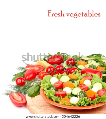 The Greek salad with cheese balls and fresh ripe vegetables and herbs on an orange plate and on a white background with a place for the text. - stock photo