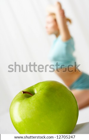 The green apple in the foreground, on a background the young girl goes in for sports - stock photo