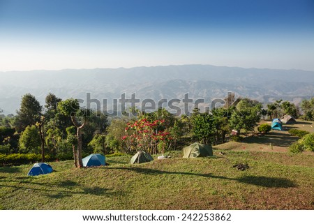 The green yard on top of mountain with tents in winter - stock photo