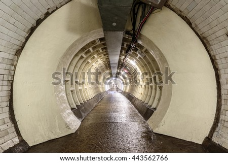 The Greenwich Foot Tunnel crosses beneath the River Thames, linking Greenwich in the south with the Isle of Dogs to the north. - stock photo