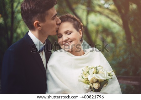 The groom and bride are walking in the park at their wedding day. The groom is kissing a bride. Couple are smiling, they are happy.  Newlyweds in love. They became husband and wife this day.  - stock photo