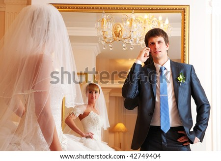 The groom and the bride against a mirror. The groom speaks by phone. - stock photo