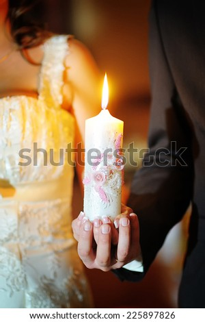 The groom and the bride with candles. Wedding ceremony in church. - stock photo