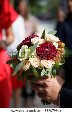 The groom brings a bouquet for the bride. Groom with bridal bouquet of roses, berries and dahlias - stock photo