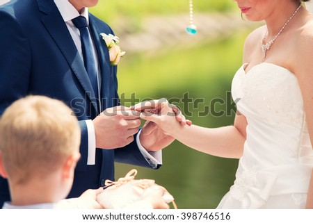 the groom dresses not weight a ring on a finger on wedding registration