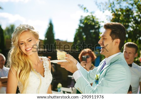 The groom feeds the bride with a piece of wedding cake